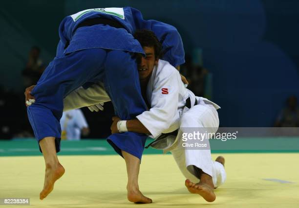 Mirali Sharipov of Uzbekistan holds Arash Miresmaeili of Iran in the Men 66 kg Preliminary contest during day 2 of the Beijing 2008 Olympic Games at...
