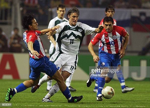 Miran Pavlin of Slovenia takes on Carlos Paredes and Roberto Acuna of Paraguay during the Slovenia v Paraguay Group B World Cup Group Stage match...