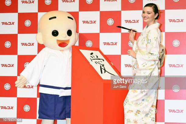 Miranda Kerr draws her new year's calligraphy 'love' during the promotional event for Marukome Kojiamazake sweet rice sake at Shinagawa Goos on...