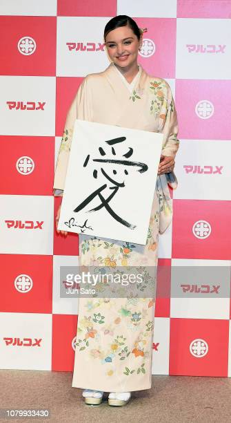 Miranda Kerr holds her new year's calligraphy 'love' during the promotional event for Marukome Kojiamazake sweet rice sake at Shinagawa Goos on...
