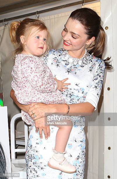 Miranda Kerr poses with a young child at a Kora Organics pop up store in Martin Place as part of Fashion's Night Out on September 6 2012 in Sydney...