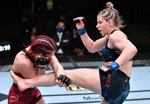 Miranda Maverick kicks Gillian Robertson of Canada in their lightweight fight during the UFC 260 event at UFC APEX on March 27, 2021 in Las Vegas,...