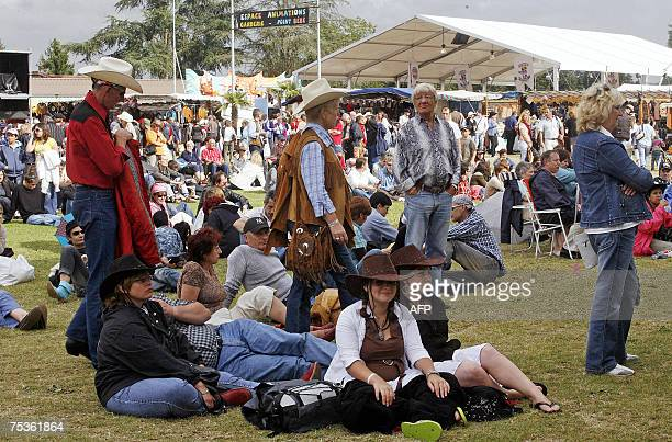 People listen to a concert during the opening of France's biggest country music festival headed this year by the Dallas cast 11 July 2007 in Mirande...