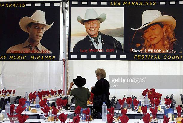 People watch pictures of France's biggest country music festival previous edition's hosts 11 July 2007 in Mirande southwest of France prior the...
