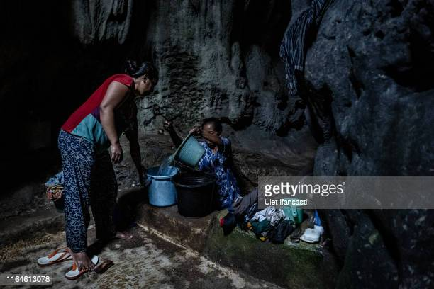 Miratin fills a bucket full of water inside a cave at Klepu village Sawahan Kulon on August 28 2019 in Pacitan East Java province Indonesia During...