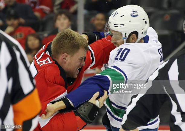 Mirco Mueller of the New Jersey Devils fights with Brandon Sutter of the Vancouver Canucks during the second period at the Prudential Center on...