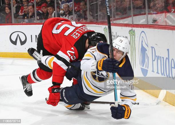 Mirco Mueller of the New Jersey Devils knocks down Evan Rodrigues of the Buffalo Sabres during the first period at the Prudential Center on February...