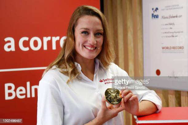 Mireia Belmonte poses for photo with her Gold Olympic Medal during her medal exhibition opening at the Santander Work Cafe Recoletos of Banco...