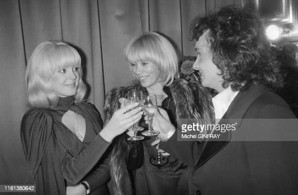 Mireille Darc trinque avec Michel Sardou et sa compagne Babette dans la loge du chanteur après son concert à l'Olympia de Paris le 30 décembre 1974...