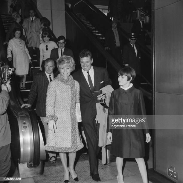 Mireille Mathieu arrive des EtatsUnis suivie de son producteur Johnny Stark de l'acteur Robert Stack et sa femme le 22 mai 1966 à Orly France