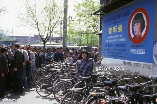 Mireille Mathieu devant une publicité la représentant Pékin le 12 mai 1986
