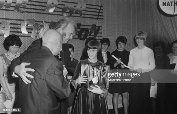Mireille Mathieu recevant la 'Note d'Or' de la chanson 1968 des mains de Jean Nohain et de Johnny Stark à Paris France le 20 novembre 1968