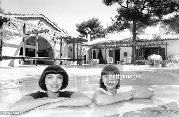 Mireille Mathieu se detend dans la piscine de la propriete de son impresario Johnny Stark pres de Marseille avec sa soeur Monique en aout 1980 a La...