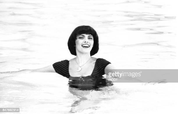 Mireille Mathieu se detend dans la piscine de la propriete de son impresario Johnny Stark pres de Marseille en aout 1980 a La Bedoule France