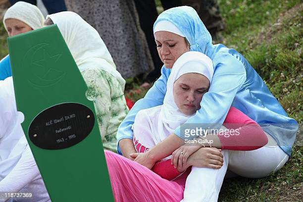 Mirela Alic is comforted by her aunt Diana Alic at the open grave of her grandfather Zajko Alic at the Potocari cemetery and memorial near Srebrenica...