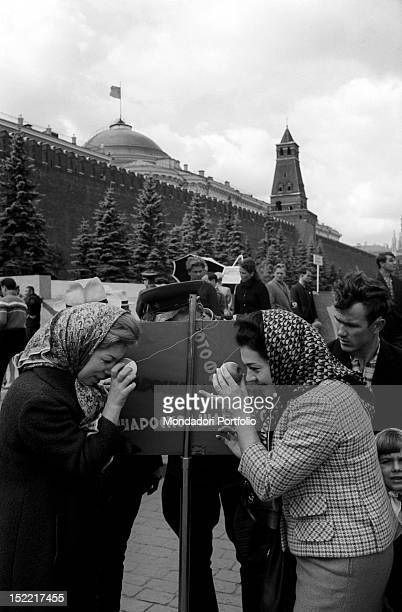 Mirella Freni is in front of Fiorenza Cossotto They are both looking through a hole in a ball Moscow September 1964