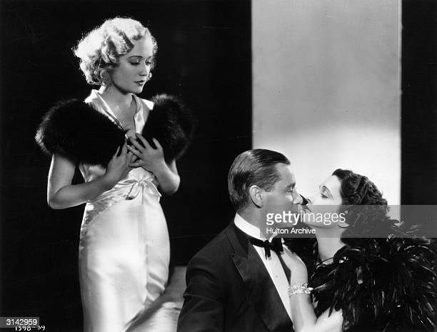 Miriam Hopkins looks on while Herbert Marshall and Kay Francis share a romantic moment during the filming of Paramount's romantic comedy 'Trouble in...