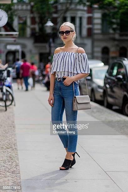 Miriam Mache wearing a white navy striped off shoulder shirt from Zara a Radley London bag blue BDG denim jeans Rodenstock sunglasses and black...