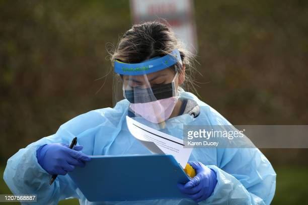Mirian Fuentes a medical assistant checks paperwork during a COVID19 screening at an appointmentonly driveup clinic set up by the University of...
