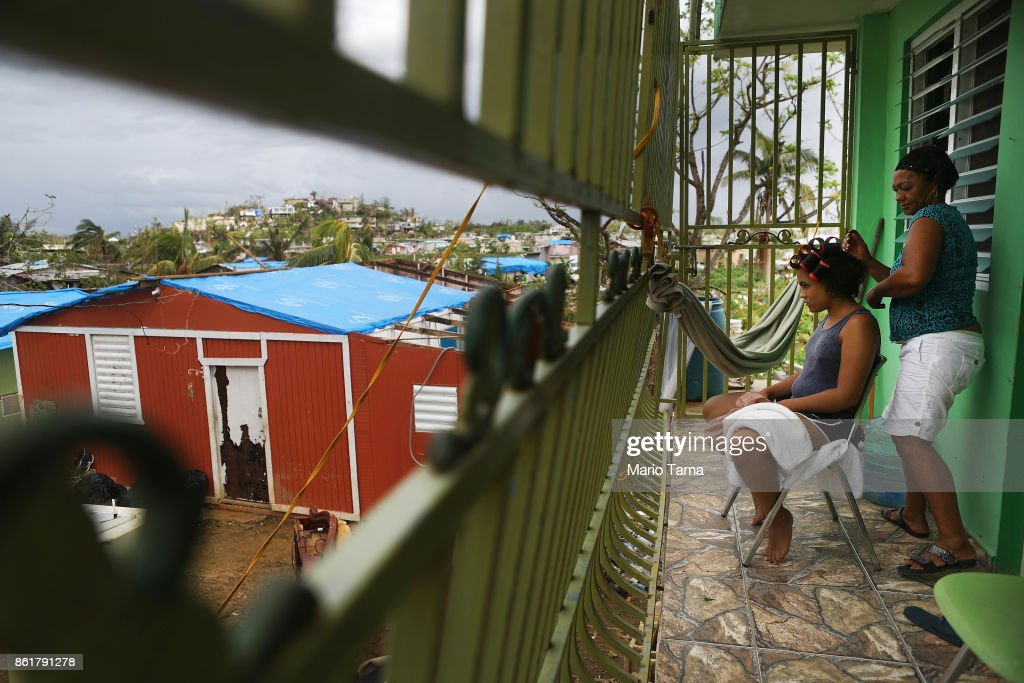 Mirian Medina does the hair of her granddaughter Nitza Flores on her fron porch, as damaged homes stand in a neighborhood area without grid electricity on October 15, 2017 in San Isidro, Puerto Rico. Puerto Rico is suffering shortages of food and water in areas and only 15 percent of grid electricity has been restored. Puerto Rico experienced widespread damage including most of the electrical, gas and water grid as well as agriculture after Hurricane Maria, a category 4 hurricane, swept through.