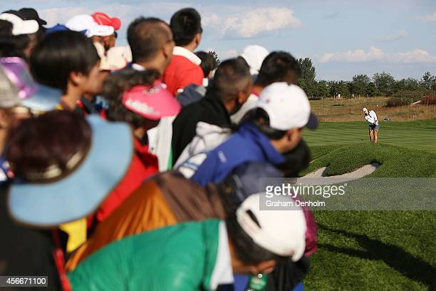 Mirim Lee of South Korea hits an approach shot watched by a large crowd during day four of the 2014 Reignwood LPGA Classic at Reignwood Pine Valley...