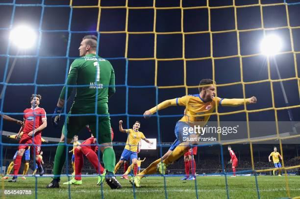Mirko Boland of Braunschweig celebrates his team's first goal as goalkeeper Kevin Mueller of Heidenheim reacts during the Second Bundesliga match...