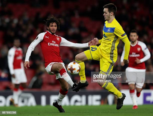 Mirko Ivanic of BATE Borisov and Mohamed Elneny of Arsenal battle for possession during the UEFA Europa League group H match between Arsenal FC and...