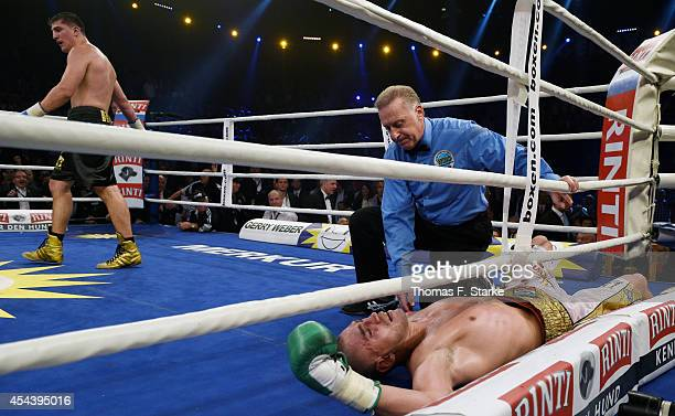 Mirko Larghetti of Italy lies on the ground while Marco Huck of Germany walks away during their WBO Cruiserweight World Championship fight at the...
