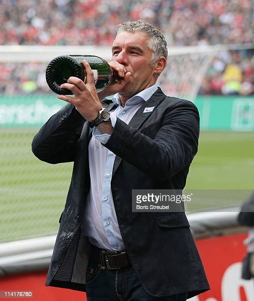 Mirko Slomka head coach of Hannover celebrates with champagne after the Bundesliga match between Hannover 96 and 1 FC Nuernberg at AWD Arena on May...