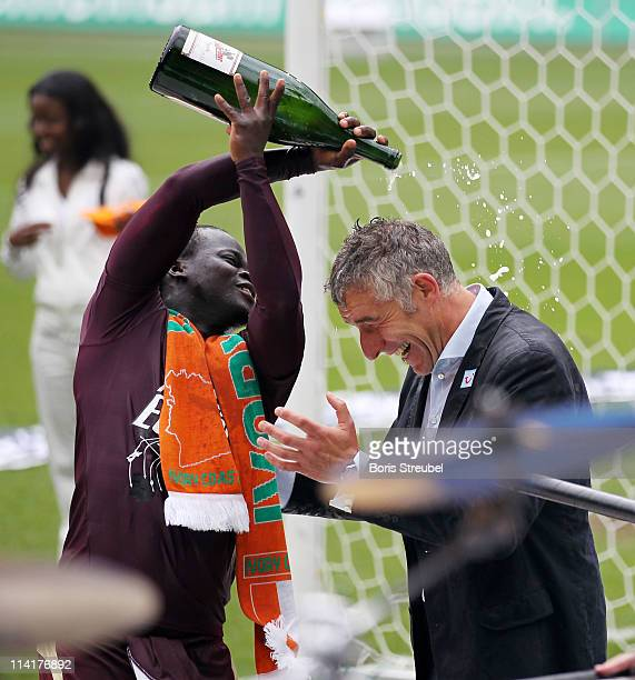 Mirko Slomka head coach of Hannover gets a champagne shower from his player Didier Ya Konan after the Bundesliga match between Hannover 96 and 1 FC...
