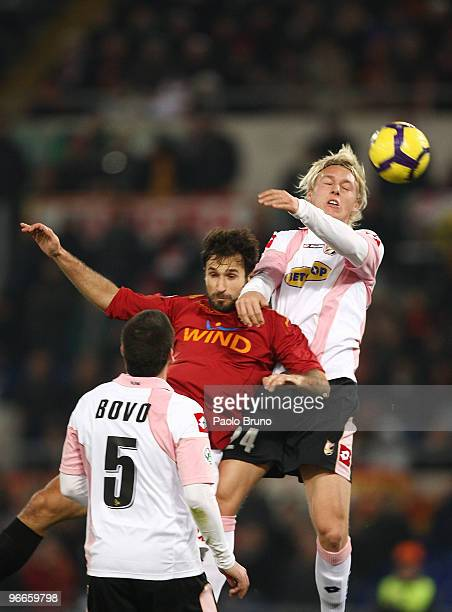 Mirko Vucinic of AS Roma and Simon Kjaer of US Citta' di Palermo in action as Cesare Bovo of US Citta' di Palermo looks on during the Serie A match...