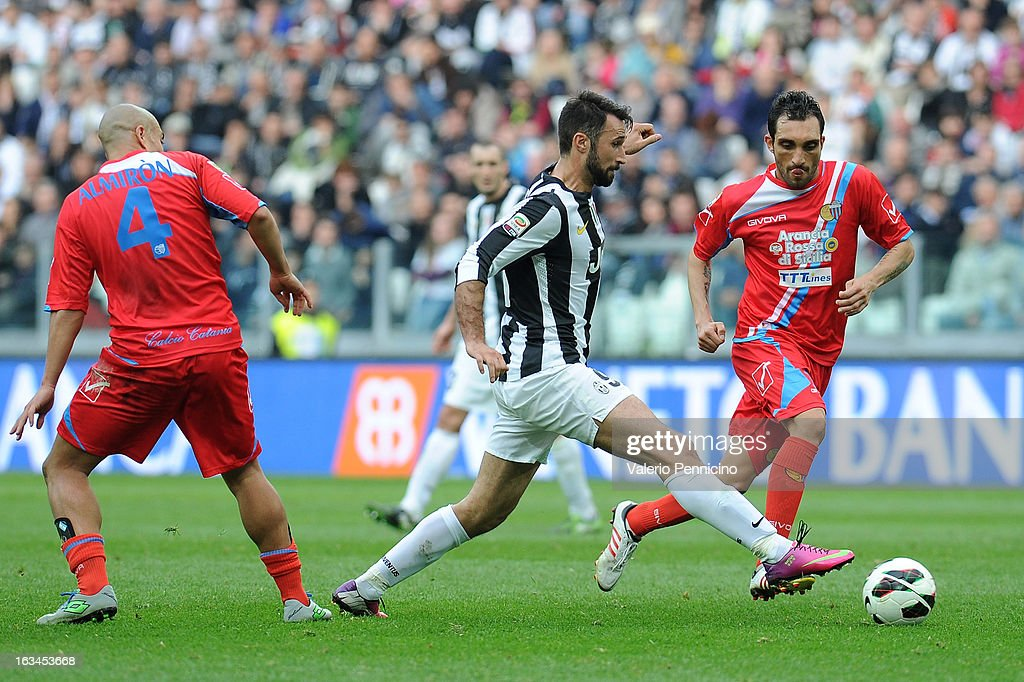 Mirko Vucinic (C) of FC Juventus is challenged by Francesco Lodi (R) of Calcio Catania during the Serie A match between FC Juventus and Calcio Catania at Juventus Arena on March 10, 2013 in Turin, Italy.