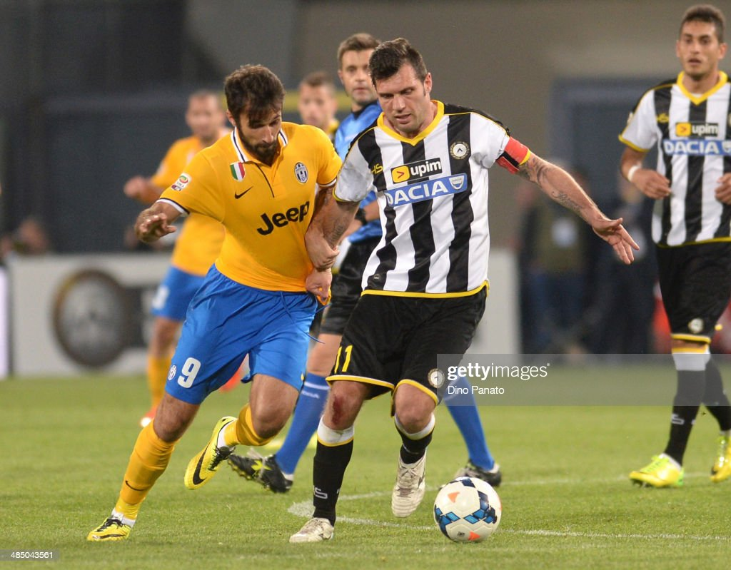Mirko Vucinic (L) of Juventus competes with Maurizio Domizzi of Udinese Calcio during the Serie A match between Udinese Calcio and Juventus at Stadio Friuli on April 14, 2014 in Udine, Italy.