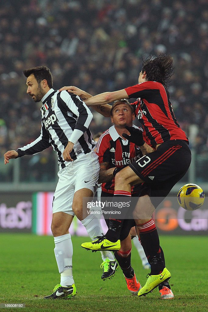 Mirko Vucinic (L) of Juventus FC clashes with Philippe Mexes (C) and Francesco Acerbi (R) of AC Milan during the TIM cup match between Juventus FC and AC Milan at Juventus Arena on January 9, 2013 in Turin, Italy.