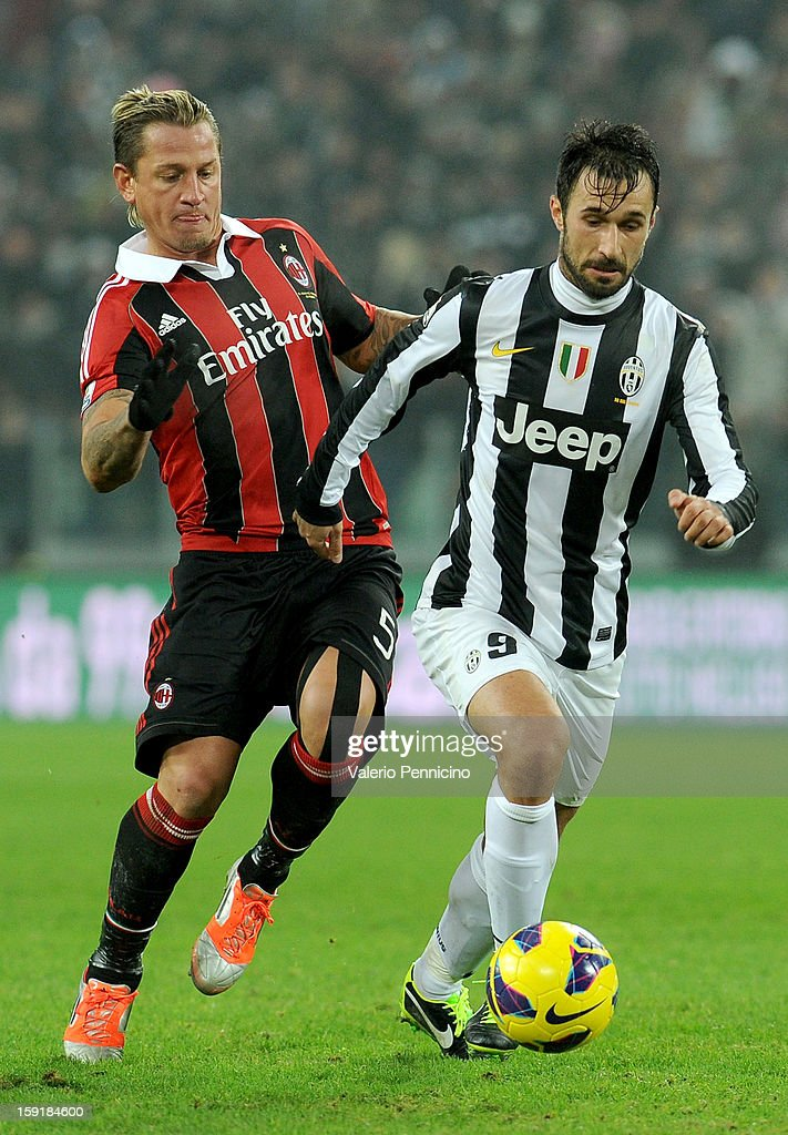 Mirko Vucinic (R) of Juventus FC in action against Philippe Mexes of AC Milan during the TIM cup match between Juventus FC and AC Milan at Juventus Arena on January 9, 2013 in Turin, Italy.