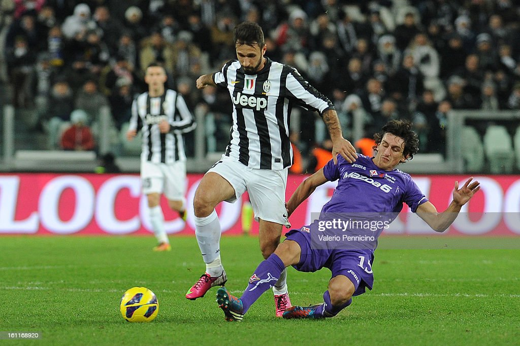 Mirko Vucinic (L) of Juventus FC is tackled by Stefan Savic of ACF Fiorentina during the Serie A match between Juventus FC and ACF Fiorentina at Juventus Arena on February 9, 2013 in Turin, Italy.