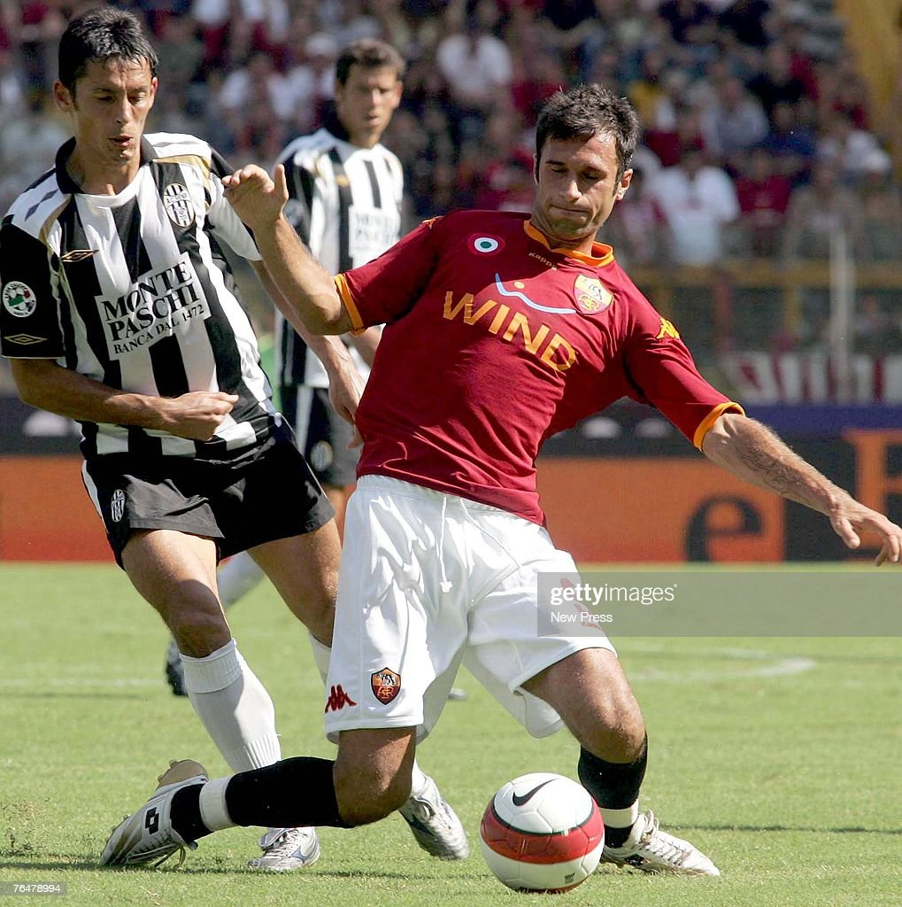 Mirko Vucinic of Roma and Paul Codrea of Siena battle for the ball during a Serie A match between Roma and Siena at the Stadio Olimpico on September 02, 2007 in Rome, Italy.
