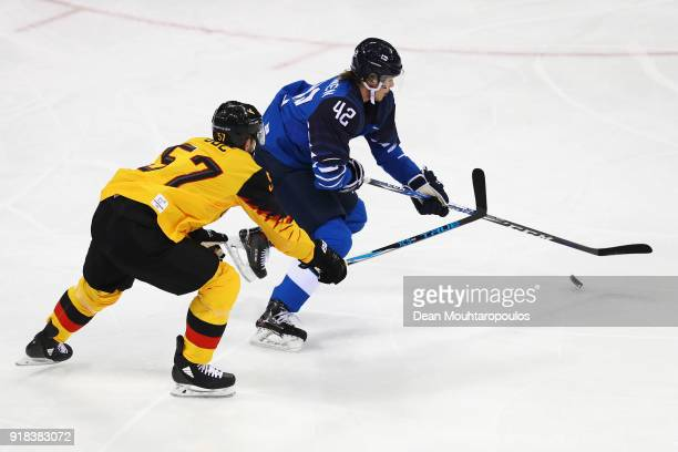Miro Heiskanen of Finland battles for the puck with Marcel Goc of Germany during the Men's Ice Hockey Preliminary Round Group C game on day six of...