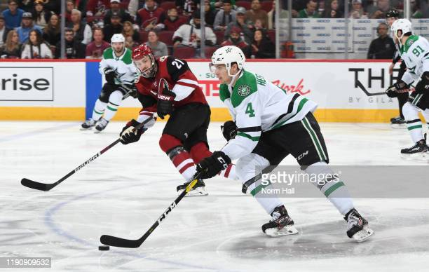 Miro Heiskanen of the Dallas Stars advances the puck up ice past Derek Stepan of the Arizona Coyotes during the second period of the NHL hockey game...