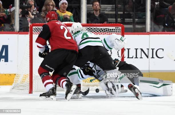 Miro Heiskanen of the Dallas Stars and Derek Stepan of the Arizona Coyotes battle for the puck in the crease as it falls under goalie Anton Khudobin...
