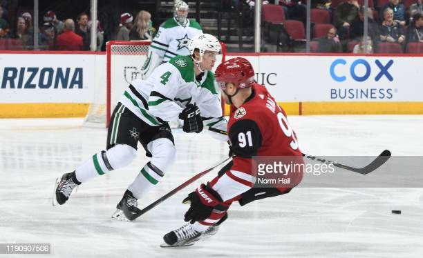 Miro Heiskanen of the Dallas Stars plays the puck around Taylor Hall of the Arizona Coyotes during the first period of the NHL hockey game at Gila...
