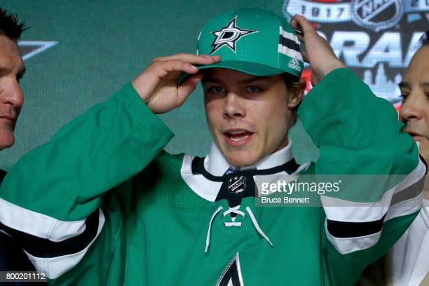 Miro Heiskanen puts on a Dallas Stars hat after being selected third overall during the 2017 NHL Draft at the United Center on June 23 2017 in...