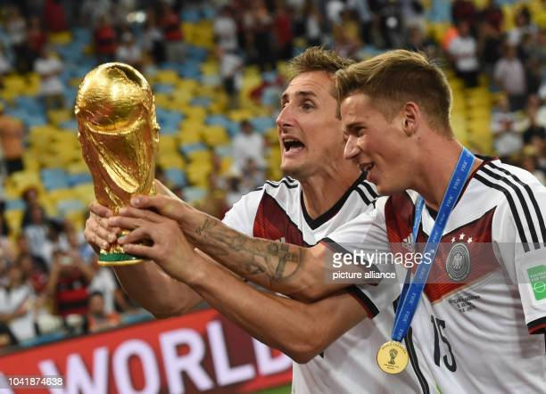 Miroslav Klose and Erik Durm celebrate with the trophy after winning the FIFA World Cup 2014 final soccer match between Germany and Argentina at the...