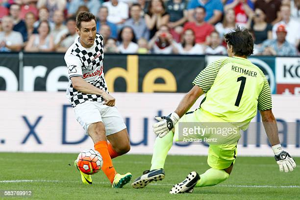 Miroslav Klose competes against Claus Reitmaier during the 'Champions for charity' football match between Nowitzki All Stars and Nazionale Piloti in...
