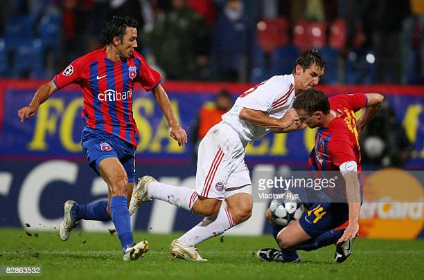 Miroslav Klose of Bayern attacks as George Ogararu and Sorin Ghionea of Bucharest defend during the UEFA Champions League Group F match between FC...
