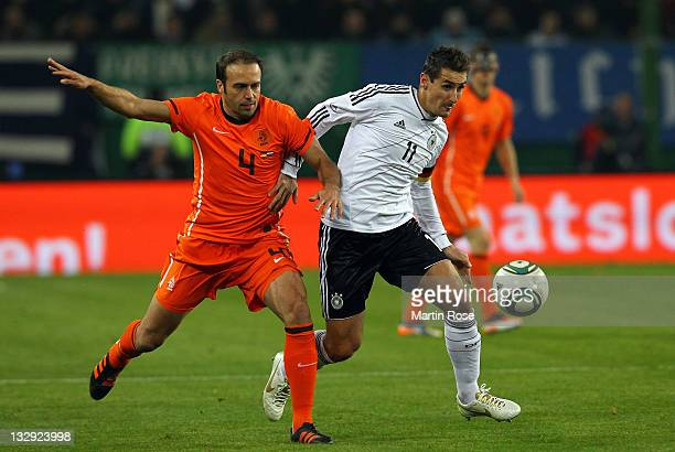 Miroslav Klose of Germany and Joris Mathijsen of Netherlands battle for the ball during the International friendly match between Germany and...
