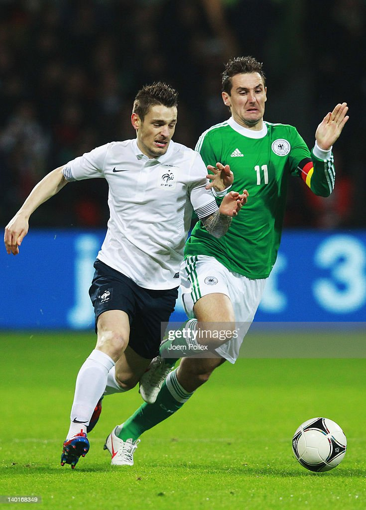 Miroslav Klose (R) of Germany and Mathieu Debuchy of France battle for the ball during the International friendly match between Germany and France at Weser Stadium on February 29, 2012 in Bremen, Germany.