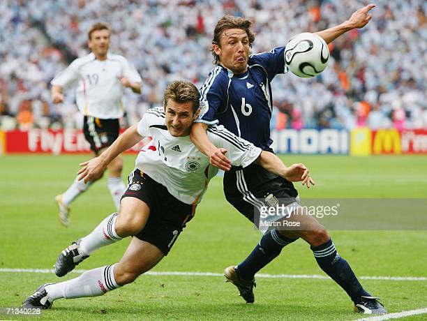Miroslav Klose of Germany battles for the ball with Gabriel Heinze of Argentina during the FIFA World Cup Germany 2006 Quarterfinal match between...