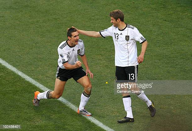 Miroslav Klose of Germany celebrates scoring the opening goal with team mate Thomas Mueller during the 2010 FIFA World Cup South Africa Round of...