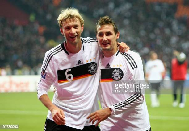 Miroslav Klose of Germany celebrates with team mate Simon Rolfes after winning the FIFA 2010 World Cup Group 4 Qualifier match between Russia and...